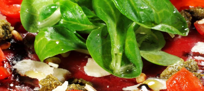 Ossenhaascarpaccio, rucola, tomaat, pijnboompitten en Parmezaan
